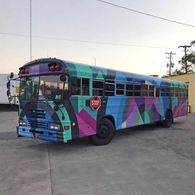 Denver street artist Jason T. Graves paints school bus for the Bus to Show company.